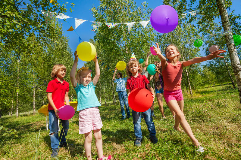 Kids playing funny game with colorful balloons stock images
