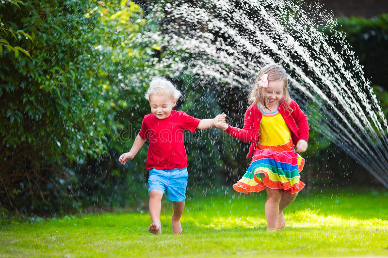 Kids playing with garden sprinkler. Child playing with garden sprinkler. Preschooler kid run and jump. Summer outdoor water fun in the backyard. Children play stock image