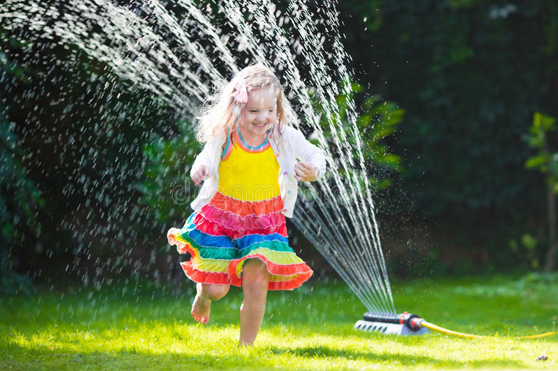 Kids playing with garden sprinkler. Child playing with garden sprinkler. Preschooler kid running and jumping. Summer outdoor water fun in the backyard. Children stock images