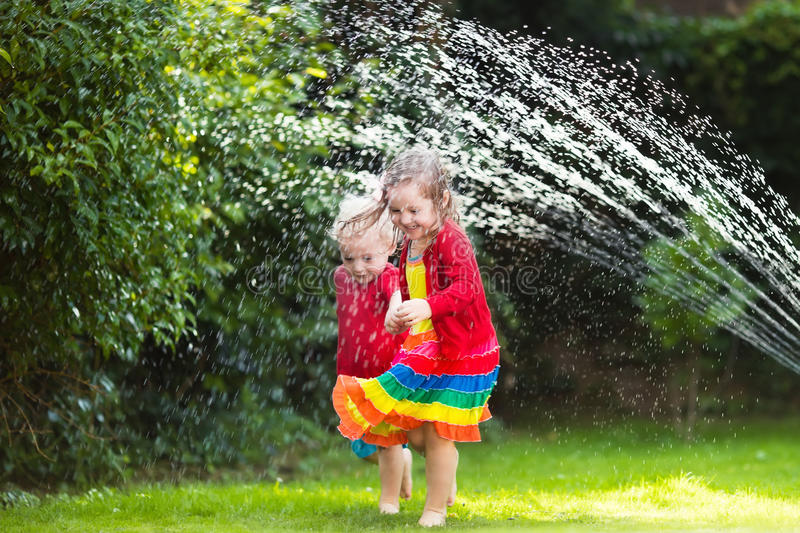 Kids playing with garden sprinkler. Child playing with garden sprinkler. Preschooler kid running and jumping. Summer outdoor water fun in the backyard. Children stock photography