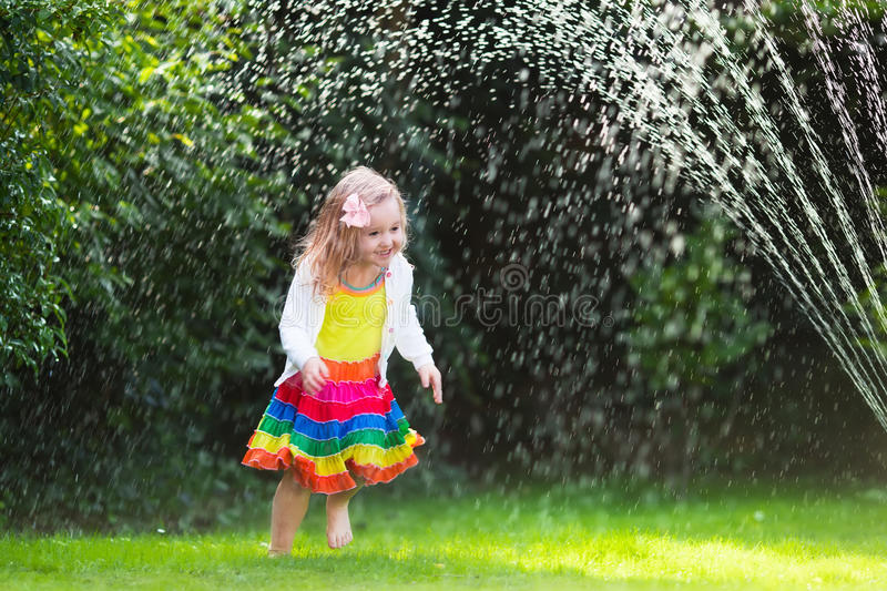 Kids playing with garden sprinkler. Child playing with garden sprinkler. Preschooler kid running and jumping. Summer outdoor water fun in the backyard. Children stock image