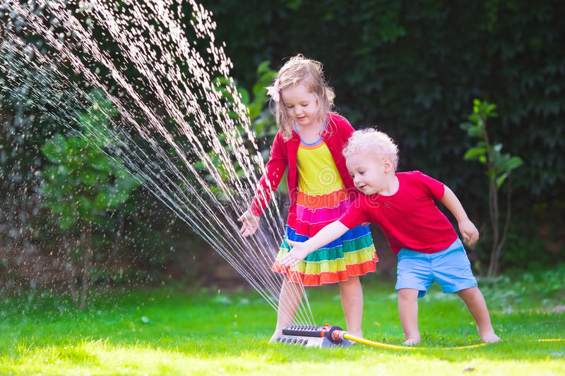 Kids playing with garden sprinkler. Child playing with garden sprinkler. Preschooler kid running and jumping. Summer outdoor water fun in the backyard. Children royalty free stock photography