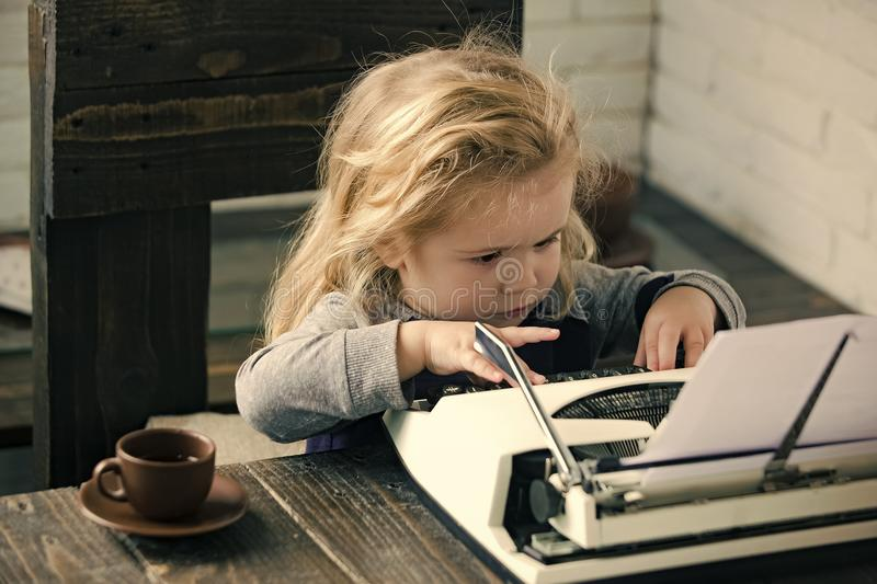 Kids playing - happy game. child or small boy or businessman kid with typewriter. Kids playing - happy game. child or small businessman kid sitting at table and royalty free stock photography