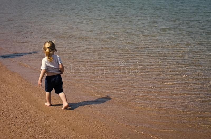 Kids playing - happy game. Kid walk on tropical beach at sea water stock image