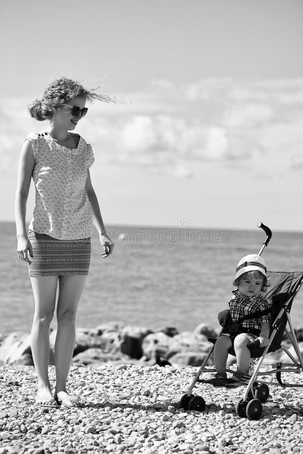 Kids playing - happy game. Mother and baby in stroller royalty free stock photography