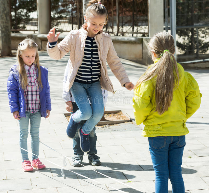 Kids playing in jump rope game. Joyful smiling kids playing in jump rope game at city street royalty free stock photo