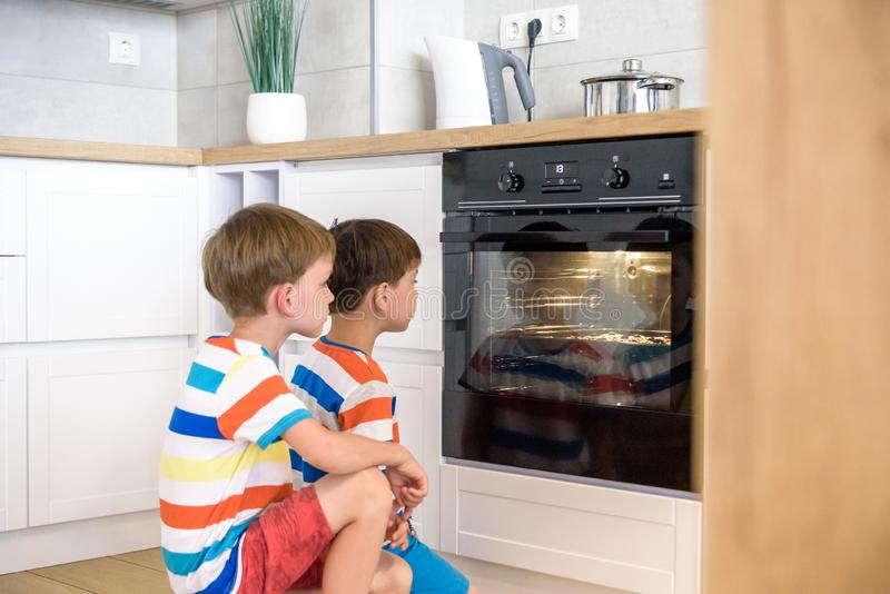 Kids playing in kitchen and waiting for preparation of biscuits in oven. two brothers sibling boys cooking at home stock photography