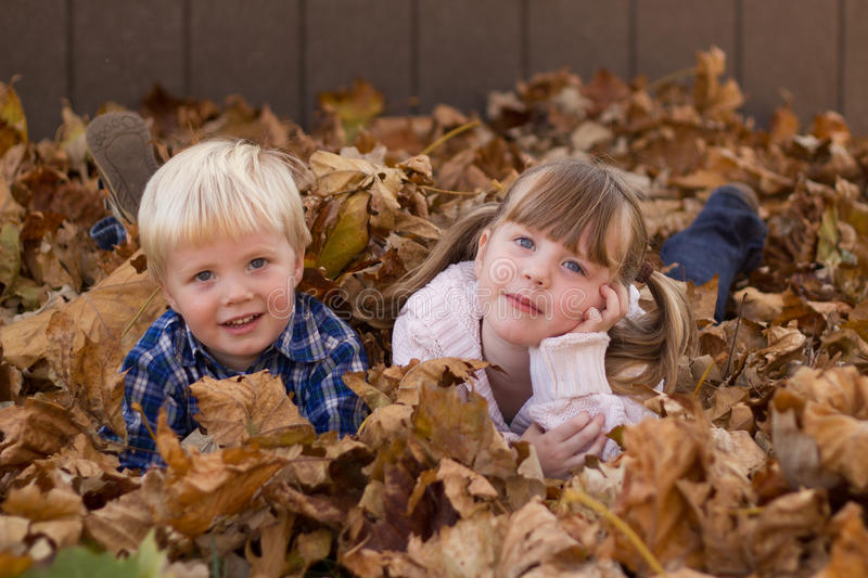 Kids playing in leaf pile leaves. Two kids, boy and girl, playing in a leaf pile, leaves royalty free stock images