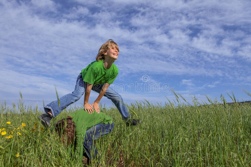 Kids playing leapfrog summer game royalty free stock photography