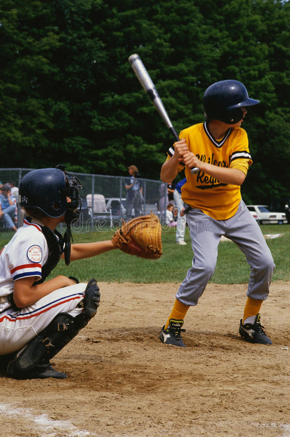 Kids playing in a little league baseball game. These are kids playing in a little league baseball game. It shows kids playing sports. There is a young boy up at royalty free stock image