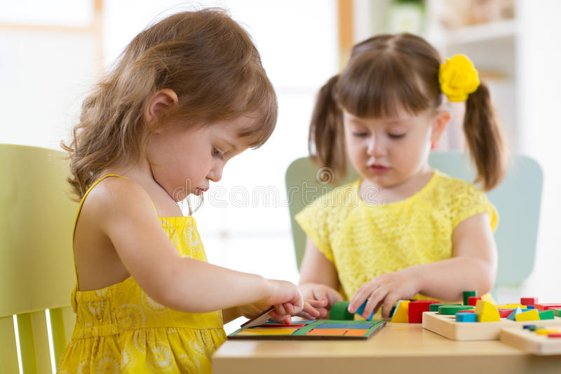 Kids playing with logical toy on desk in nursery room or kindergarten. Children arranging and sorting shapes, colors and stock photo