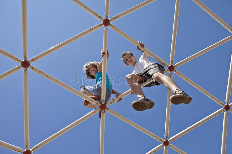 Kids playing on monkey bars royalty free stock photo
