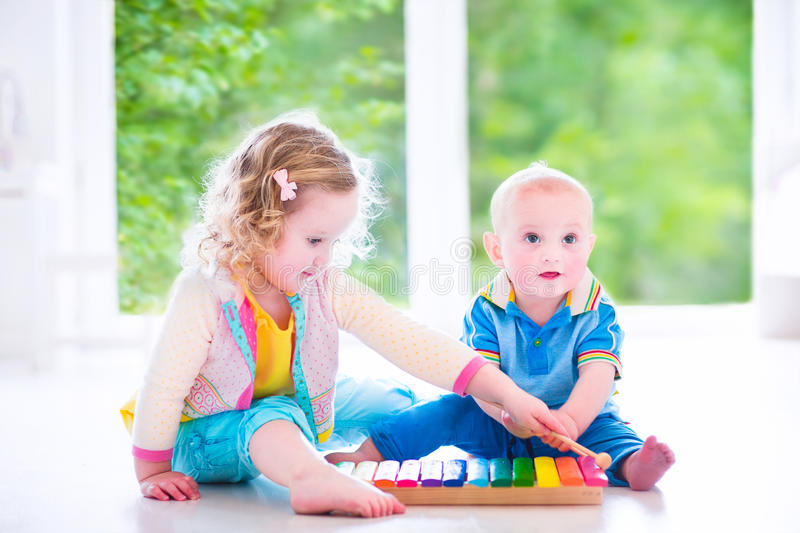 Kids playing music with xylophone. Two little children - cute curly toddler girl and a funny baby boy, brother and sister playing music, having fun with colorful stock photography