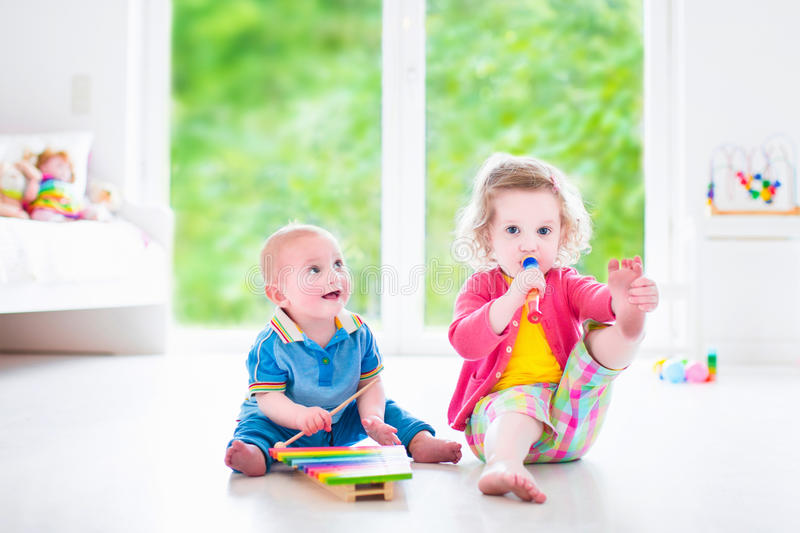 Kids playing music with xylophone. Two little children - cute curly toddler girl and a funny baby boy, brother and sister playing music, having fun with colorful stock photos