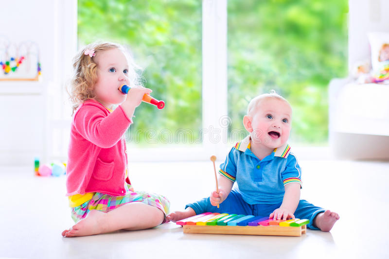 Kids playing music with xylophone. Two little children - cute curly toddler girl and a funny baby boy, brother and sister playing music, having fun with colorful stock image