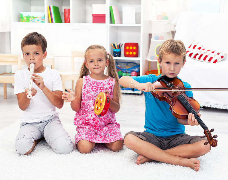 Kids playing on musical instruments. Our first band - Kids playing on musical instruments stock image