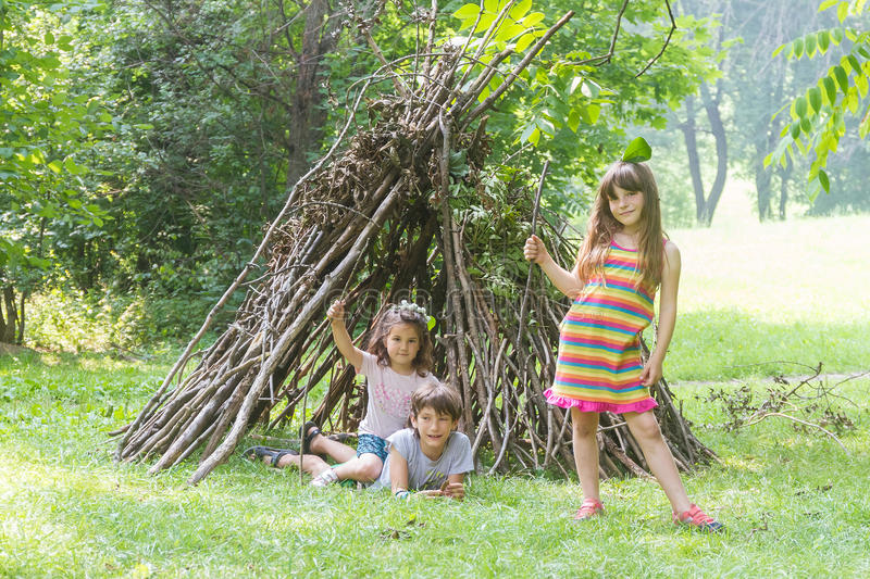 kids playing next to wooden stick house looking like indian hut, tepee stock image