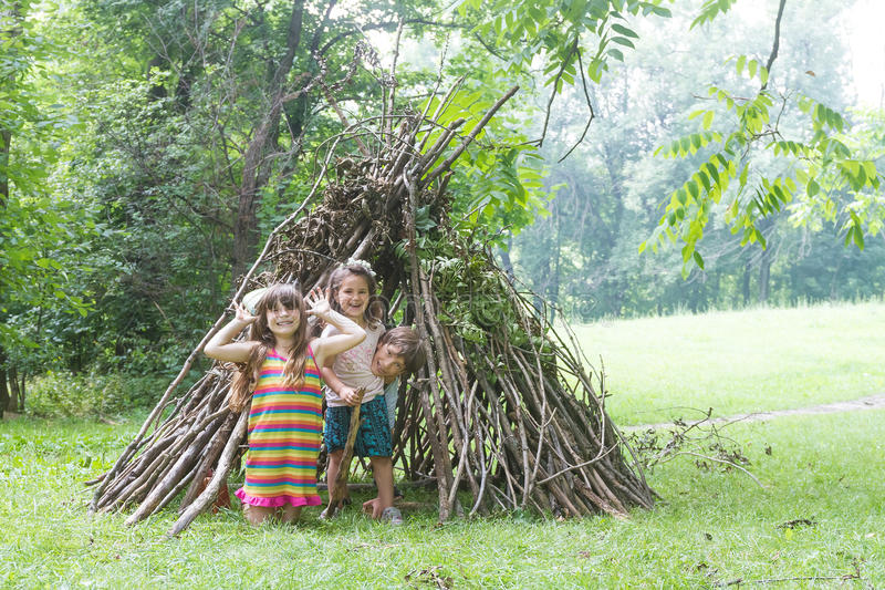 kids playing next to wooden stick house looking like indian hut, tepee stock images