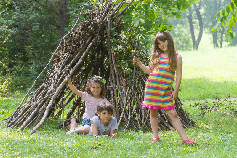 kids playing next to wooden stick house looking like indian hut, tepee royalty free stock image