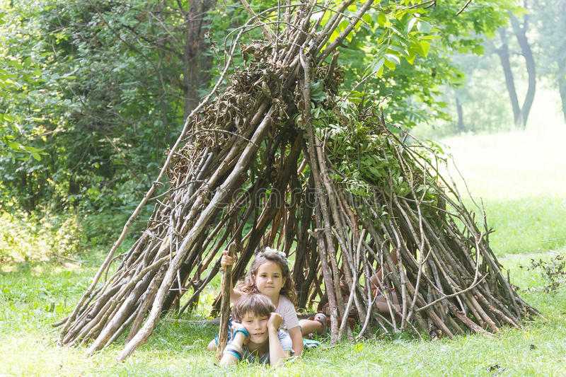kids playing next to wooden stick house looking like indian hut, tepee royalty free stock photography