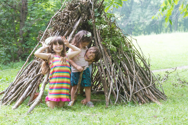 kids playing next to wooden stick house looking like indian hut, tepee stock photos
