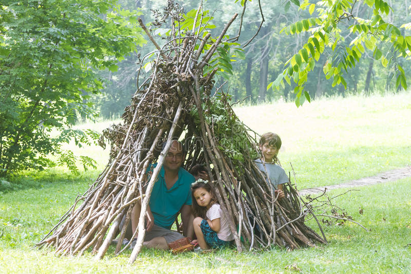 kids playing next to wooden stick house looking like indian hut, tepee stock photo
