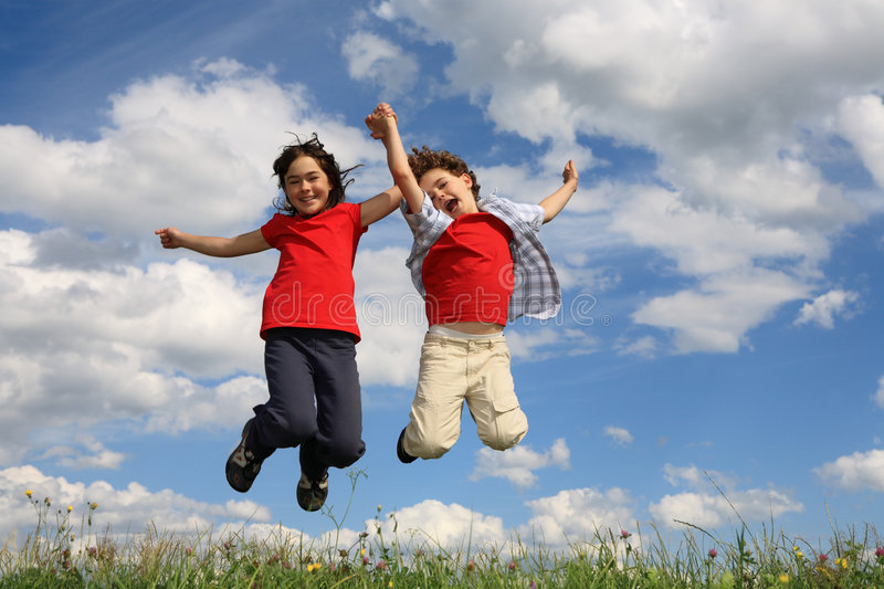 Kids playing outdoor. Kids running, jumping on green meadow against blue sky royalty free stock image