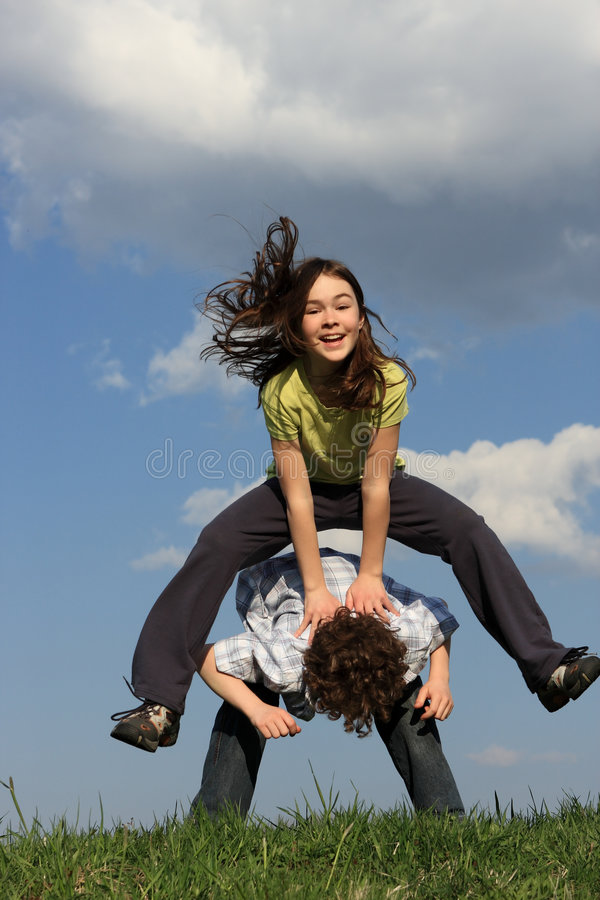 Kids playing outdoor. Kids running, jumping on green meadow against blue sky stock photos