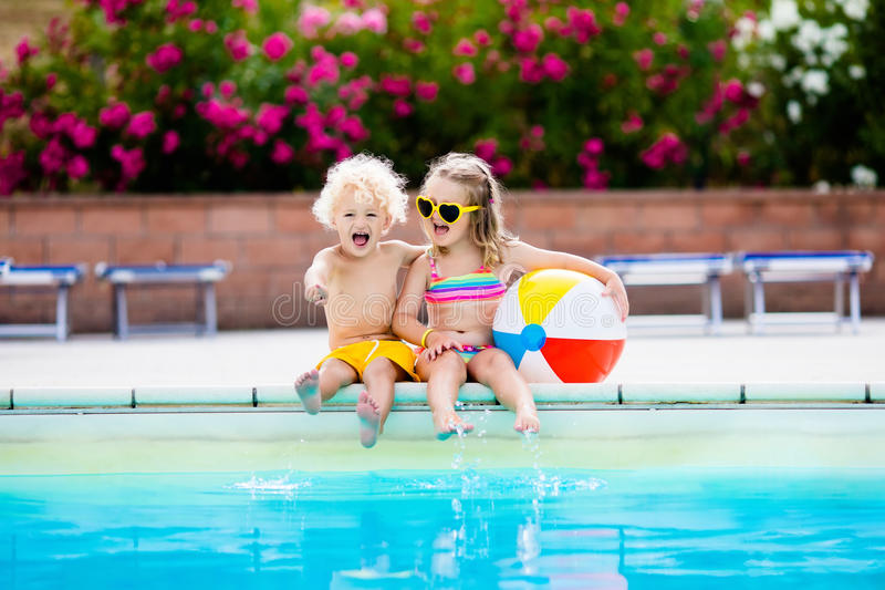 Kids playing at outdoor swimming pool. Little girl and boy play and swim in resort pool on tropical beach island summer family vacation. Swim and eye wear, sun royalty free stock images