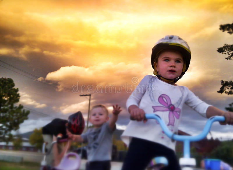 Kids playing outdoors. On bikes with dramatic skies (mobile phone image
