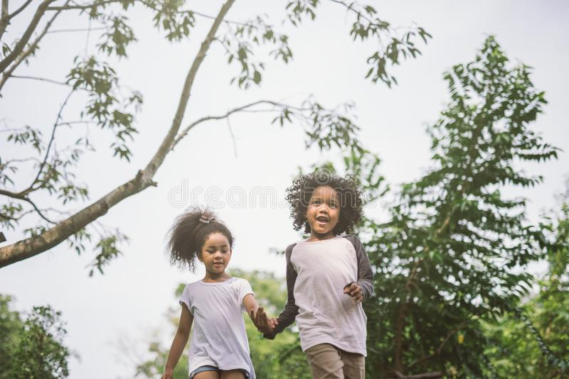 Kids playing outdoors with friends. little children play at nature park. stock photos