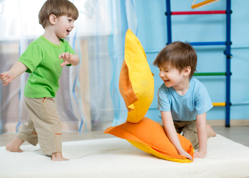 Kids playing with pillows stock images