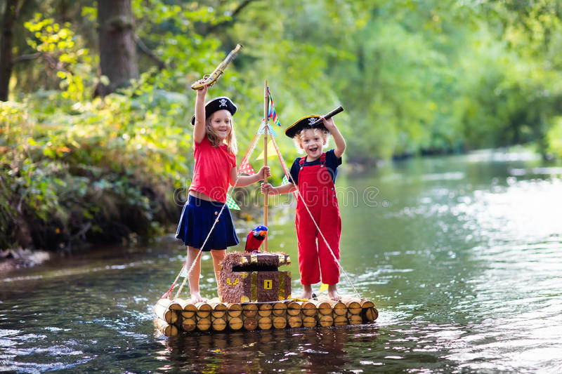 Kids playing pirate adventure on wooden raft royalty free stock image