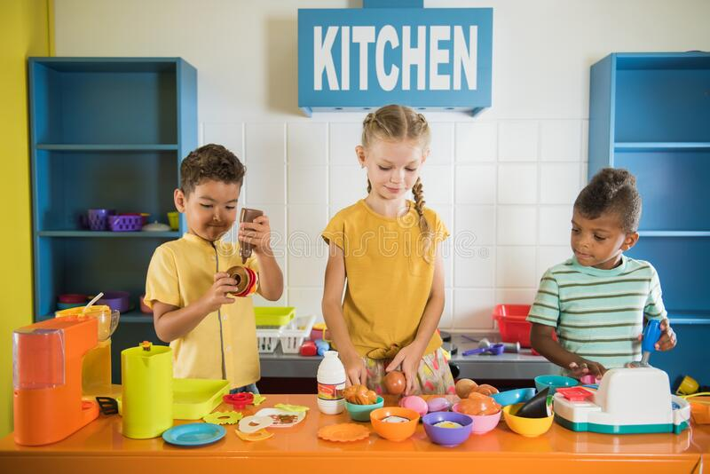 Kids playing with plastic food at daycare. Two boys and one girl playing in childrens room. Entertainment center and childrens game stock photos