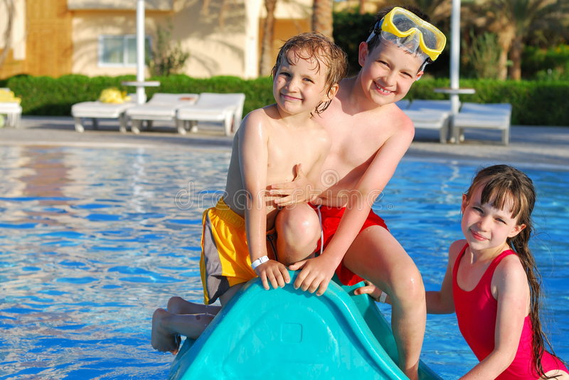 Kids playing in pool stock photography