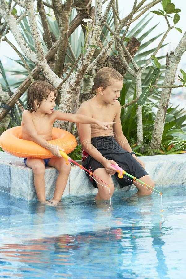 Kids playing in pool royalty free stock images