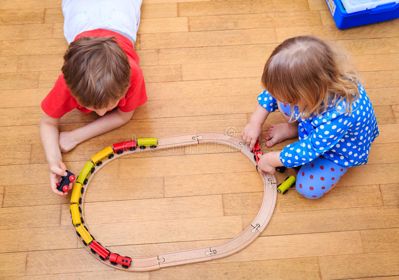 Kids playing with railroad and trains indoor. Education and daycare stock images