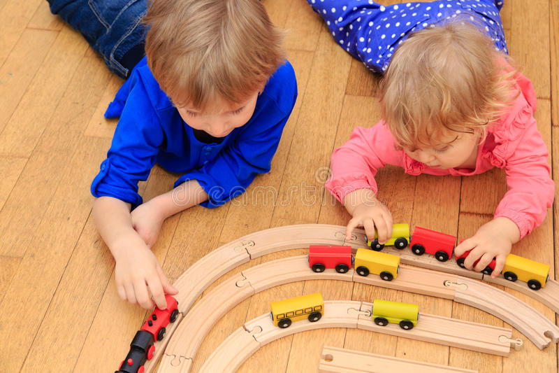 Kids playing with railroad and trains indoor. Learning and daycare stock photography