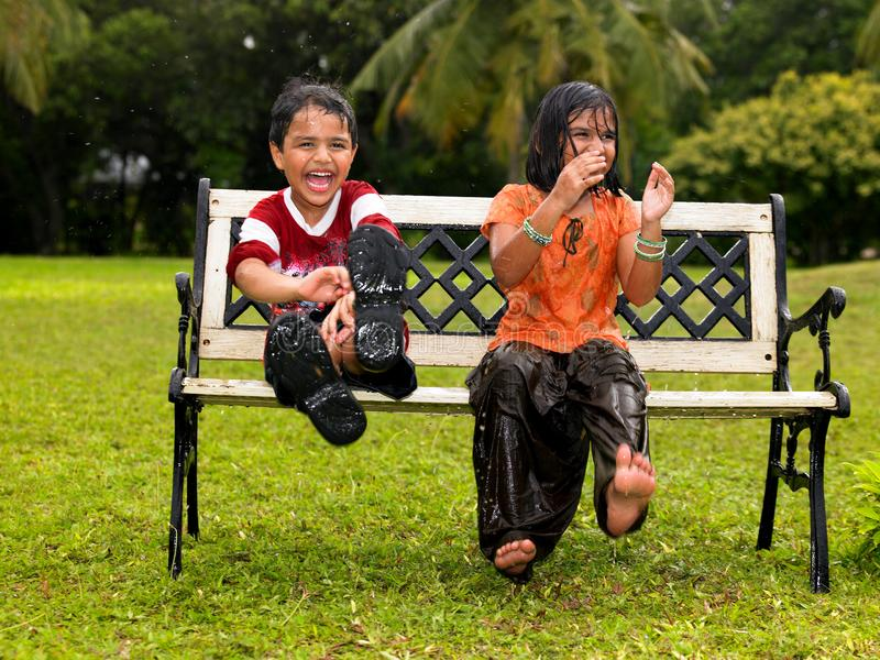 Kids playing in the rain royalty free stock photography