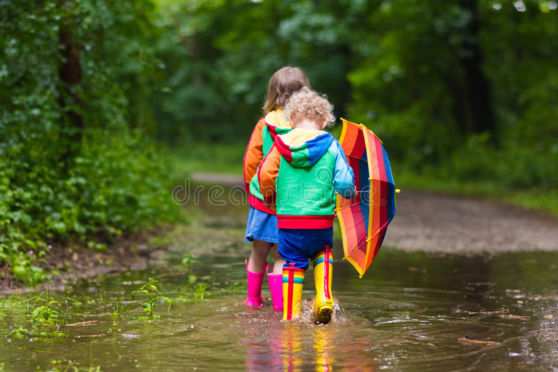 Kids playing in the rain with umbrella royalty free stock photo