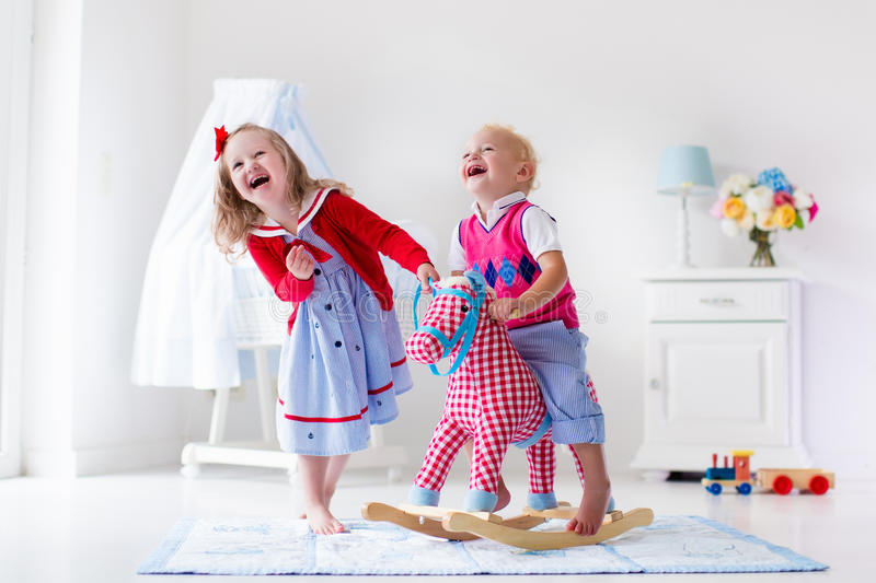 Kids playing with rocking horse royalty free stock images