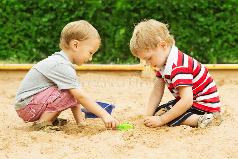 Kids Playing in Sand, Two Children Boys Outdoor Leisure in Sandbox royalty free stock image