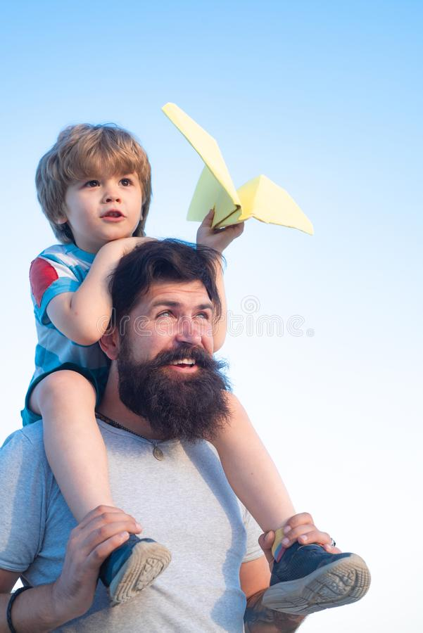 Kids playing with simple paper planes on sunny day. Father giving son ride on back in park. Father and son playing -. Family time together. Happy fathers day stock photo