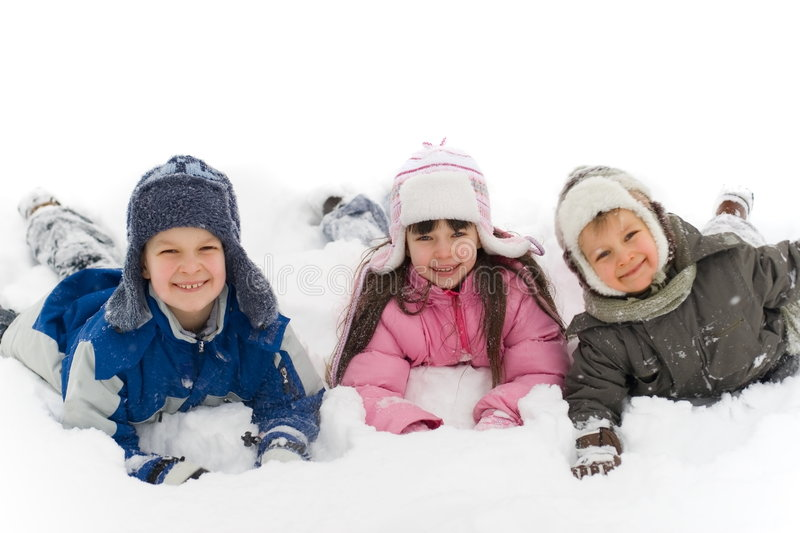 Kids Playing in the Snow. Three children having a lot of fun, all dressed for winter, playing in the snow stock photography