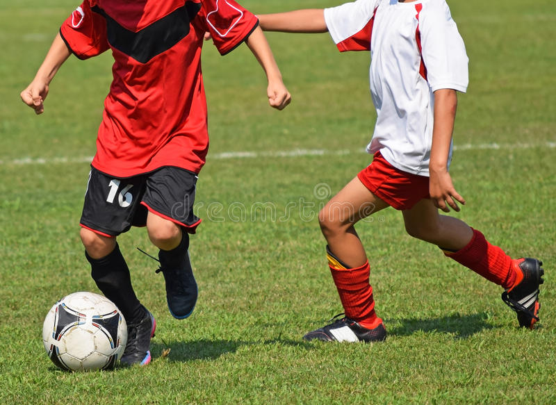 Kids are playing soccer. Outdoors in summer stock image