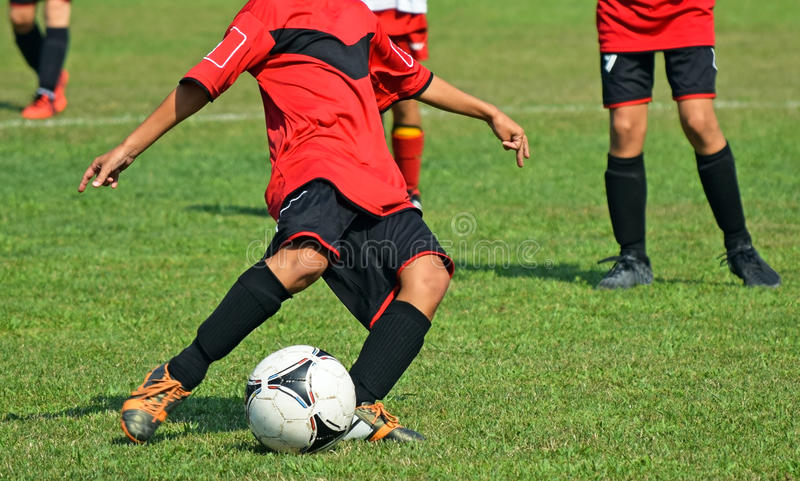 Kids are playing soccer. In summer stock photography