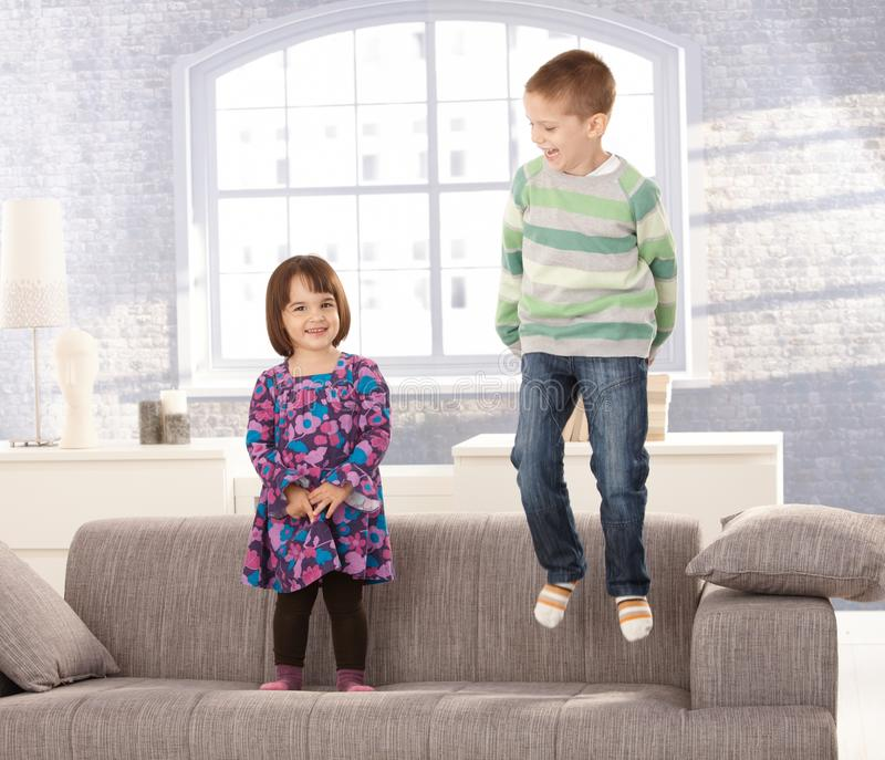 Kids playing on sofa. Little boy jumping, small girl standing, laughing stock photos