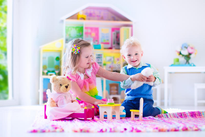 Kids playing with stuffed animals and doll house royalty free stock images