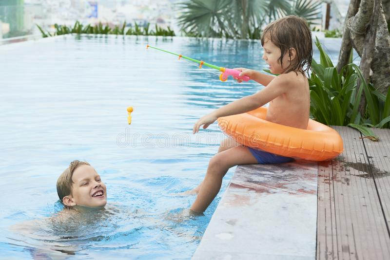 Kids playing in swimming pool stock photography