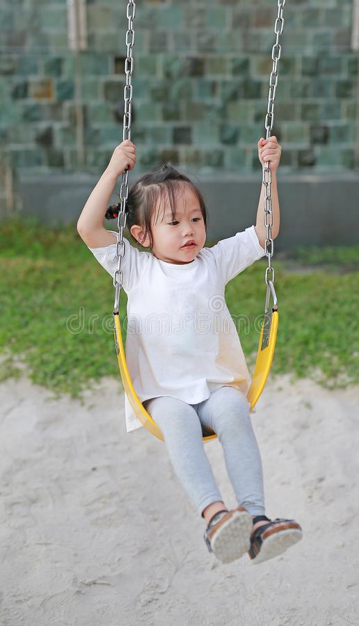 Kids playing at the swing in the playground. Kids girl playing at the swing in the playground stock photos